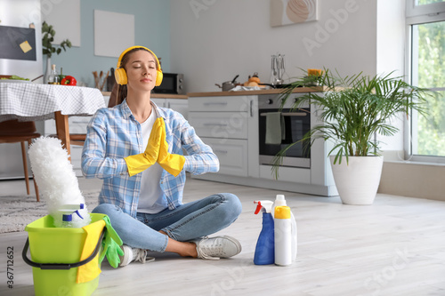 Obraz Beautiful young woman meditating during cleaning of kitchen - fototapety do salonu