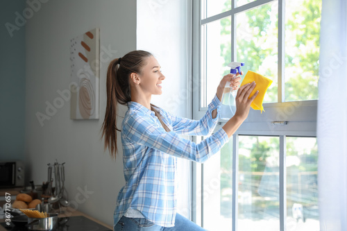 Cuadros en Lienzo Beautiful young woman cleaning window at home
