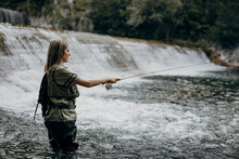 Young Adult Woman Is Fishing Alone On Fast Mountain River. Active People And Sport Fly Fishing Concept.
