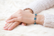 Flower Bracelet On Young Woman Hand Wrist On White, Fluffy Fur Blanket. Skin Care And Beauty In Winter Time. Closeup.