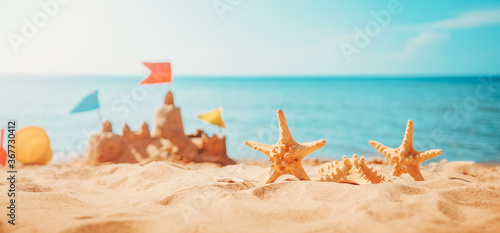 Sandcastle on the beach at sea in summertime - 367730412
