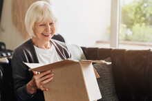 Happy Senior Grey-haired Woman Sitting On Couch Opening Carton Box Received Parcel Package, Internet Order