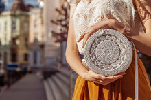 Close Up Of Bag In Fashionable Elegant Woman`s Outfit: Trendy White Wicker Small Round Shoulder Bag. Model Posing In Street Of European City. Copy, Empty Space For Text
