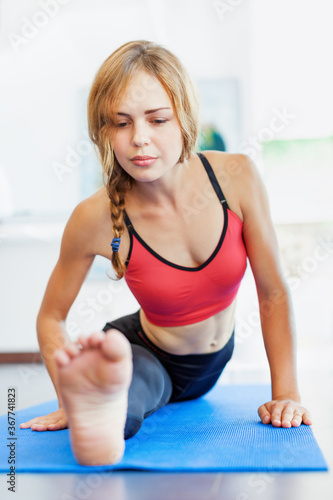 Young active woman doing front split stretching exercise