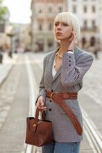 Street Fashion Photo Of Elegant  Woman Wearing Trendy Checkered Blazer, Wide Wicker Belt, Holding Brown Faux Croco Leather Textured Bag. Model Walking In Street Of European City