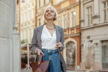Street Fashion Portrait Of Happy Smiling  Woman Wearing Trendy Checkered Blazer, High Waist Jeans, Holding Brown Faux Croco Leather Textured Bag. Model Posing In Street Of European City. Copy Space