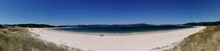 Panoramic Shot Of A White Beach Shoreline On  A Clear Blue Sky Background