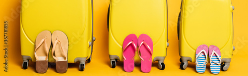 travel bags with family flip flops isolated on yellow, panoramic shot