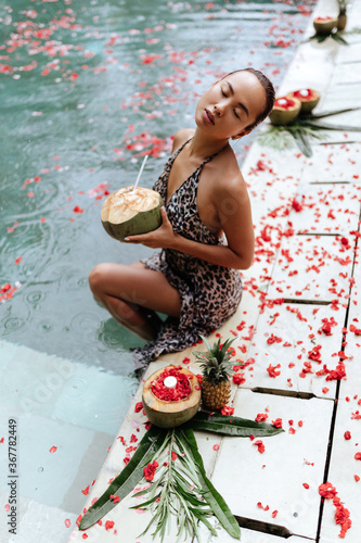 Happy woman relaxing in the swimming pool and drinking coconut water