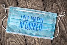 Face Masks Required - Text On A Disposable Mask, Business Sign During The Coronavirus Covid-19 Pandemic And Social Distancing