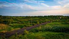 Colour Landscape Photograph Of Train Tracks Cutting Through A Lush Marsh In The Afternoon In Kingston, Ontario Canada In The Late Summer.