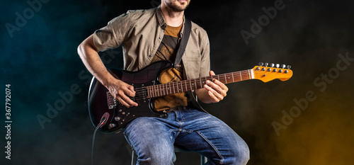 Obraz Jazz guitar player performing on electric guitar. Male guitarist musician plays blues and jazz. - fototapety do salonu