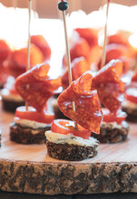 Black Rye Bread Appetizer With Spanish Chorizo Sausage, Tomato And Cheese Served On Wooden Tray Outdoors. Mini Sandwiches. Party Snacks, Party Food.