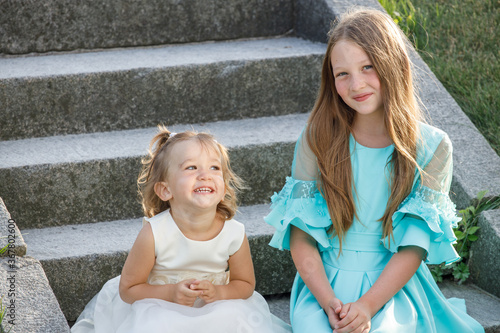 Photo two sisters sitting on the stairs in the summer in the park