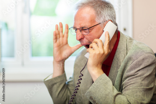 Obraz Portrait of an angry businessman yelling at phone - fototapety do salonu