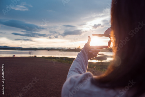 Fototapeta The woman making frame round the sun with her hands in sunrise,Future planning idea concept,copy space,warm retro tone. obraz