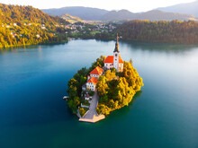 Aerial View Of Beautiful Lake Bled In The Middle Of The Charming Little Island And The Wonderful Church At Summer Sunrise