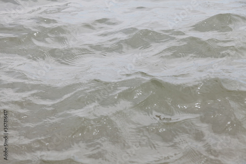Cuadros en Lienzo Close-up of a river with undulating waves with muddy gray water in cloudy weather