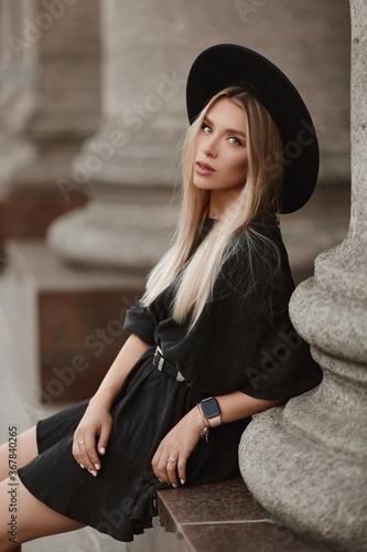 Young model girl with blond hair in a trendy hat and black dress posing outdoors at the city