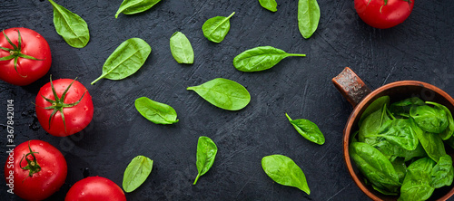 Carta da parati Fresh grape tomatoes with spinach Leaves on black stone background