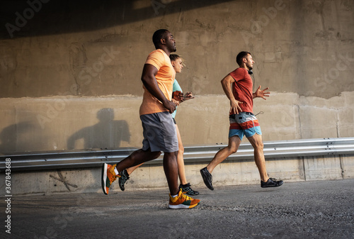 Obraz Group of friends jogging at the city street. Multi ethnic group of people. - fototapety do salonu