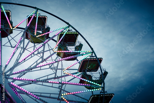 Colorful ferris wheel at dusk, illuminated by neon lights Fototapet
