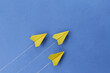 Yellow paper planes on a blue background. The concept of moving towards success.