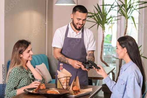 Fotografie, Obraz Woman paying bill in restaurant through terminal