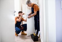Best Men At Work. Full Length Shot Of Two Locksmith, Repairmen, Workers In Uniform Installing, Working With House Door Lock Using Screwdriver. Repair, Door Lock Service Concept