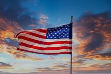 The American Flag Unfurling In Wind On Clear Blue Sky