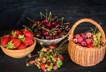 Different Berries Raspberries In A Basket, Strawberries In A Cup And Cherries In A Clay Plate On A Black Wooden Table