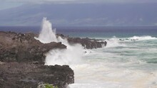 Large Wave Crashes On Rocky Hawaiian Coastline In Maui. Rough Dangerous Surf Fills The Coast As Tourists Take Photos In The Distance. Molokai In The Background.