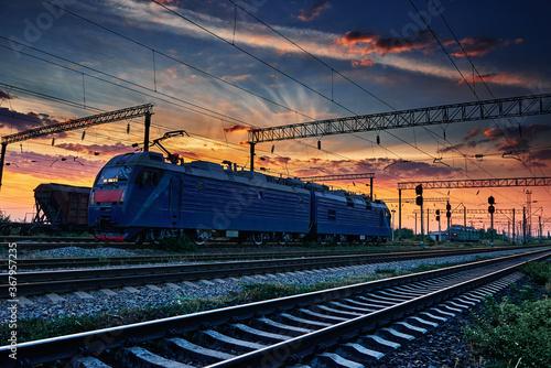Obraz na płótnie railway train and rail cars in a beautiful sunset, dramatic sky and sunlight