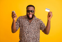 Photo Of Crazy Funny Dark Skin Guy Hold Telephone Make Online Payment Purchase Transfer Use Credit Card Wear Sun Glasses Golden Necklace Leopard Shirt Isolated Bright Yellow Background