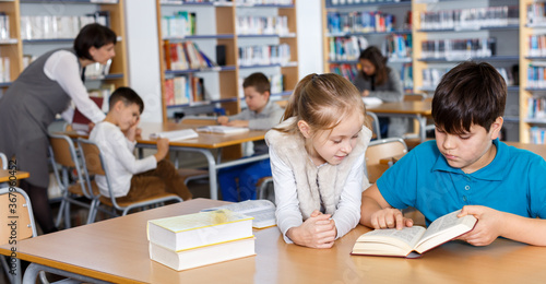 Photo Portrait of two school children preparing for lesson in school library, reading