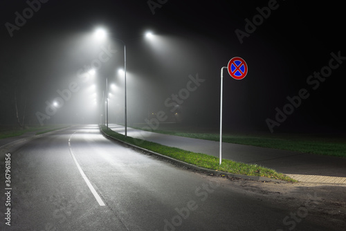 Fototapeta Illuminated empty highway in a fog at night. Street lights and road signs close-up. Dark urban scene, cityscape. Riga, Latvia. Dangerous driving, speed, freedom, concept image obraz