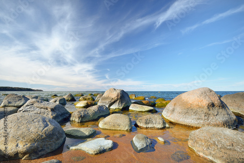 Rocky shore of the Baltic sea under a clear blue sky with cirrus clouds Fotobehang