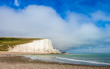 Dramatic White Cliffs, Blue Sky And Shingle Beach At Cuckmere Haven, Seven Sisters Country Park, England
