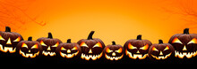 Nine Halloween, Jack O Lanterns, With Evil Spooky Eyes And Faces Isolated Against A Orange And Yellow Lit Background.