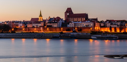 Sightseeing of Poland. Cityscape of Torun old town and Vistula river at night. UNESCO world heritage in Poland