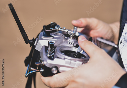 Hands holding a silver fpv drone transmitter Fotobehang