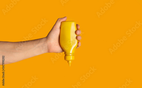 Tablou Canvas Male hand squeezing bottle with mustard on orange background, closeup