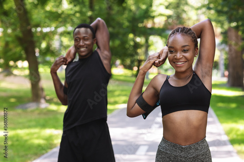 Obraz Sporty african couple exercising before jogging at park, stretching arm muscles outdoors - fototapety do salonu