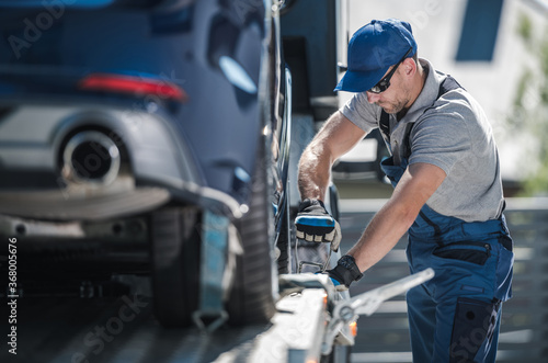 Obraz Towing Company Worker Securing Vehicle on the Truck Platform - fototapety do salonu