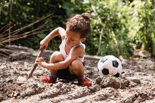 Obraz Poor african american child holding wooden twig near soccer ball on dirty road on urban street - fototapety do salonu