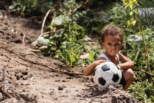 Obraz Poor african american boy holding football while sitting near plants on dirty road - fototapety do salonu