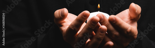 Fotografie, Obraz horizontal crop of priest holding burning candle isolated on black