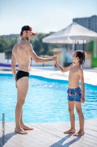 Man and boy standing opposite each other near pool