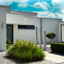 Front Garden Of A Modern Minimalist House With Stone Pillars And A Grass Turf In A Gravel Bed, View From Public Ground