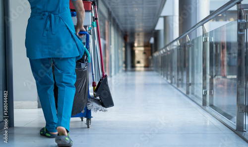 Fotografia, Obraz A woman worker in special clothes rolls a trolley for cleaning offices